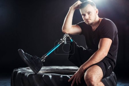 paralympic sportsman resting on tire