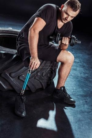 paralympic sportsman exercising with dumbbell