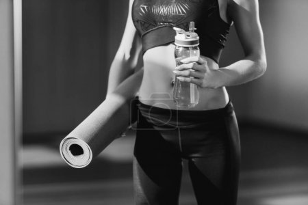 Woman with yoga mat and water