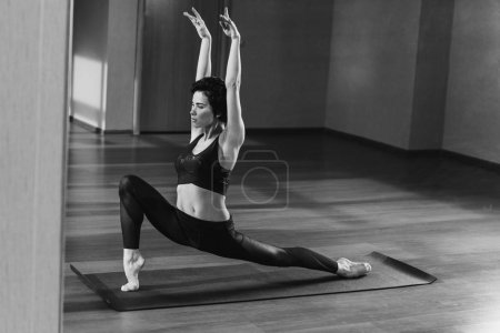 Photo for Black and white shot of woman in warrior pose practicing yoga - Royalty Free Image