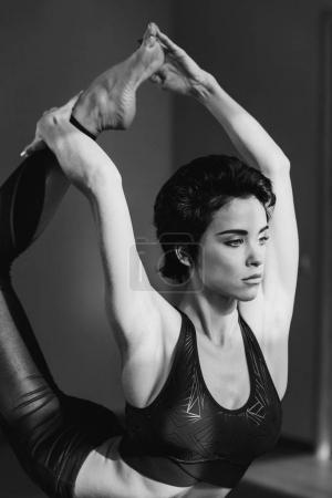 woman stretching leg behind head