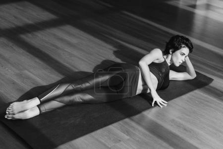 sportive woman relaxing on yoga mat