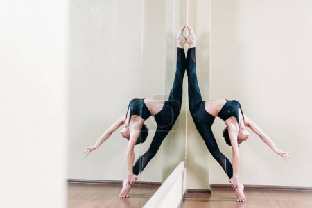 Woman doing stand split at mirror