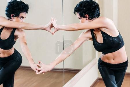 Woman touching her reflection in mirror