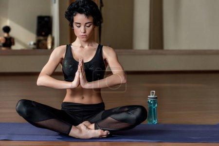 Photo pour Belle femme méditant assis en posture de lotus sur le tapis d'yoga - image libre de droit