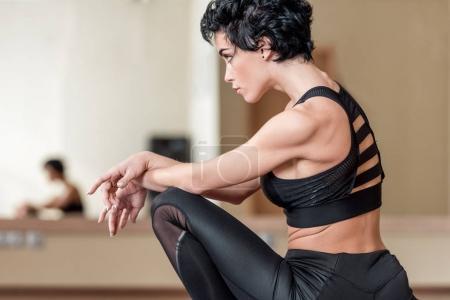 Photo pour Jeune femme sportive, assis dans la salle de danse - image libre de droit