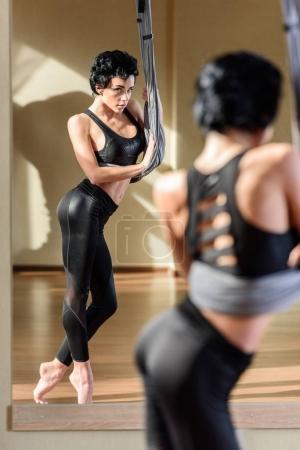Photo pour Jeune femme sensuelle, pratiquant la danse aérienne acrobatique et regardant miroir - image libre de droit