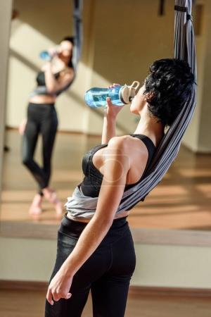 Photo pour Eau potable femme après la pratique de la danse aérienne acrobatique - image libre de droit
