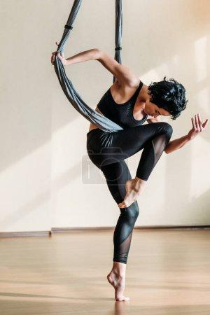 Photo pour Belle femme sportive pratiquant la danse aérienne acrobatique - image libre de droit