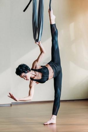 Photo pour Jeune femme sportive en tenue de sport pratiquant la danse acrobatique aérienne - image libre de droit