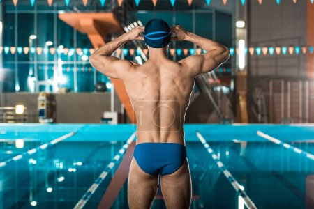 Photo for Back view of muscular swimmer in swimming cap and goggles standing at swimming pool - Royalty Free Image