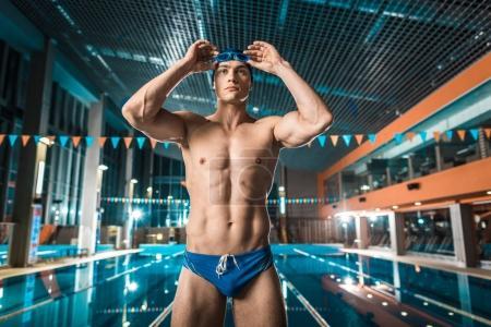 Photo pour Nageur musclé en casquette et lunettes de protection permanent à la piscine de natation - image libre de droit