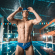 Muscular swimmer in swimming cap and goggles stand...