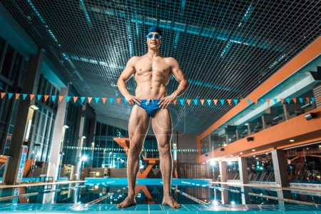Photo for Handsome muscular swimmer in swimming cap and goggles posing at swimming pool - Royalty Free Image