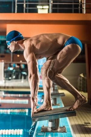 swimmer ready to jump into swimming pool