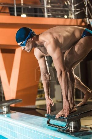 Photo for Swimmer standing on diving board ready to jump into competition swimming pool - Royalty Free Image