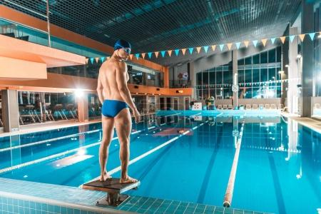 muscular swimmer at competition pool