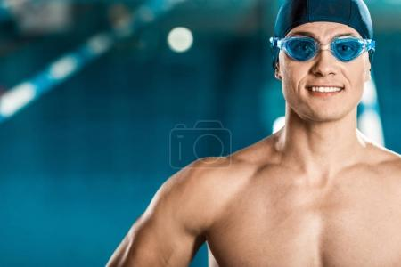 smiling muscular swimmer in swimming cap