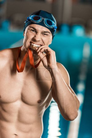 Photo for Swimmer biting medal while standing at competition swimming pool - Royalty Free Image