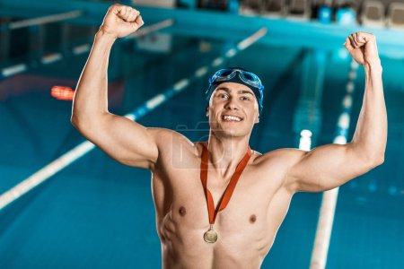 Photo for Winner with medal standing at competition swimming pool - Royalty Free Image