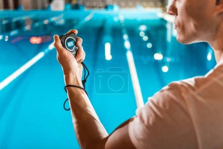 Photo for Cropped view of swim trainer with stopwatch standing at competition swimming pool - Royalty Free Image