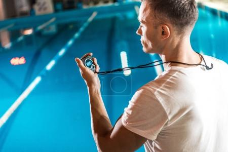Photo for Handsome swim trainer with stopwatch standing at competition swimming pool - Royalty Free Image