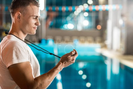 trainer with stopwatch at swimming pool