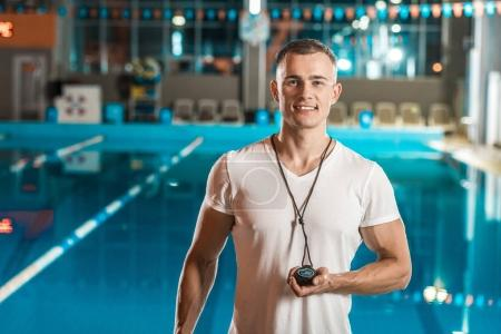 Photo for Handsome swim trainer with stopwatch at competition swimming pool - Royalty Free Image