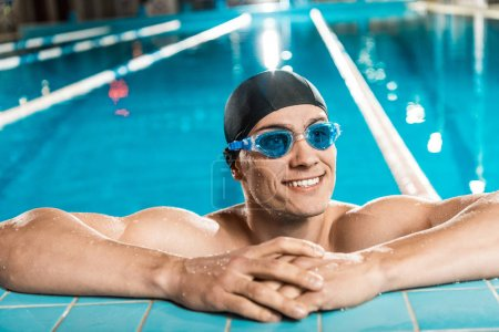 Photo for Handsome muscular swimmer in swimming cap and goggles in swimming pool - Royalty Free Image