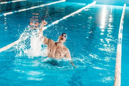 Photo for Handsome winning muscular swimmer in competition swimming pool - Royalty Free Image