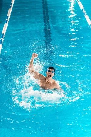 Photo for Excited swimmer gesturing and making splash in competition swimming pool - Royalty Free Image