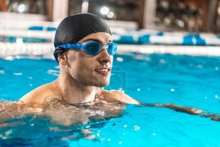 Photo pour Sportif souriant en bonnet de bain et lunettes de natation dans la piscine - image libre de droit