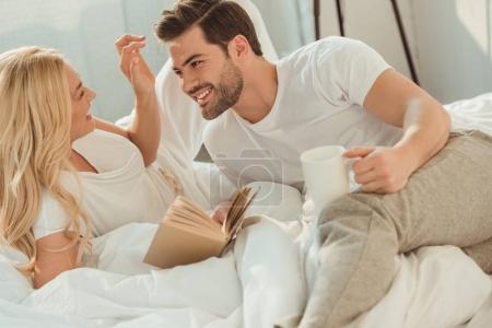 Photo pour Jeune couple heureux boire du café et lire le livre au lit le matin - image libre de droit