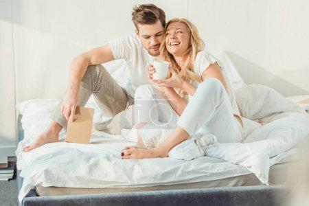 Foto de Joven pareja feliz tomando café en la cama por la mañana - Imagen libre de derechos