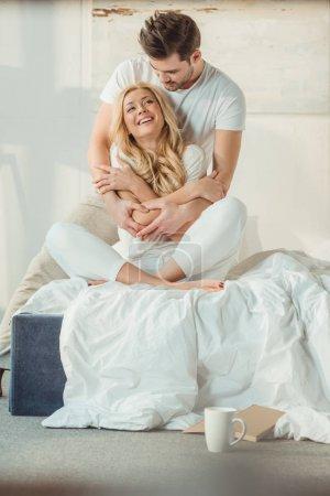 Photo pour Heureux beau couple emracing sur lit le matin - image libre de droit