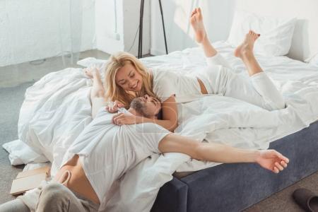Photo pour Jeune beau couple câlin au lit le matin - image libre de droit