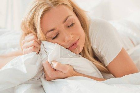 Photo pour Jeune belle femme se détendre au lit le matin - image libre de droit
