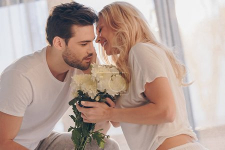 Photo pour Homme présentant des fleurs pour belle jeune copine le matin - image libre de droit
