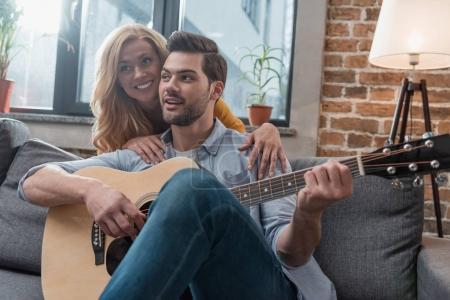 man playing guitar for girlfriend