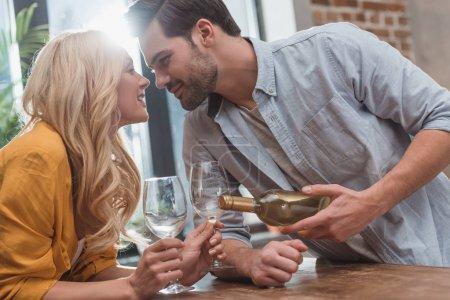 Photo pour Beau couple heureux avec bouteille de vin et verres à la maison - image libre de droit