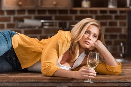 Photo for Drunk young woman with glass of wine relaxing on table at kitchen - Royalty Free Image