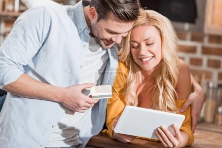 Photo pour Sourire beau couple faisant e-shopping avec tablette - image libre de droit