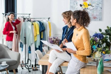 Foto de Sonrientes jóvenes diseñadores de moda mantener bocetos y notebook y mirando al compañero de pie junto a la ropa en perchas - Imagen libre de derechos