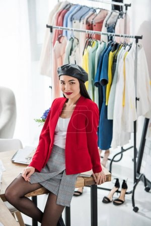 Photo for Beautiful young asian fashion designer smiling at camera at workplace - Royalty Free Image