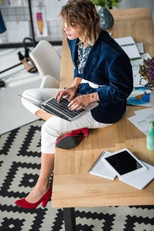 Photo for High angle view of young fashion designer using laptop while sitting on table - Royalty Free Image