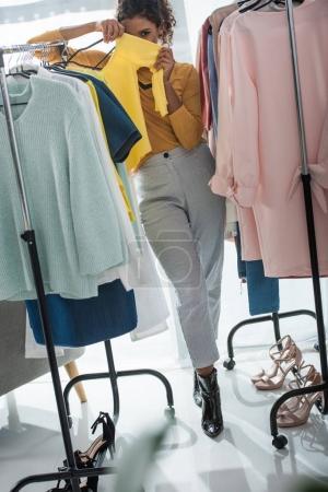 Photo pour Jeune créateur de mode afro-américain debout entre cintres avec des vêtements et en regardant la caméra - image libre de droit
