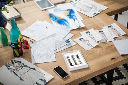 Photo for Smartphone, digital tablet with multimedia website and fashion sketches on table - Royalty Free Image