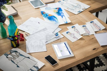 Photo for Smartphone, digital tablet with facebook website and fashion sketches on table - Royalty Free Image