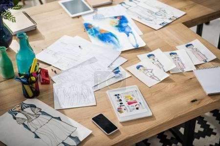 digital devices and sketches on table