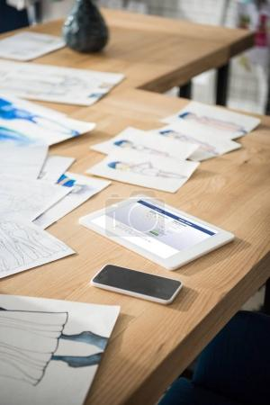 Photo for Close-up view of smartphone, digital tablet with facebook website and fashion sketches on table - Royalty Free Image